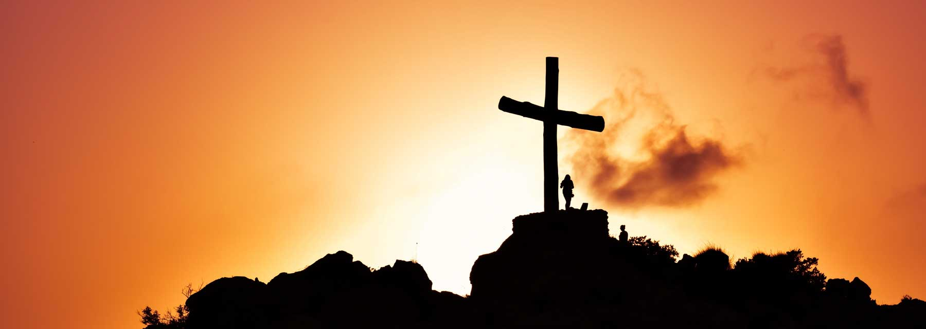 A large cross and person silhouetted against an orange sky
