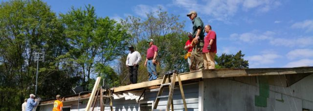 People working on the roof of a house during a mission